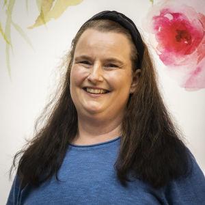 en kvinna med långt lockigt brunt hår som ler stort och har på sig en blå tröja