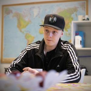 Patrik Lindblom istuu pöydän äärellä lippis päässään.