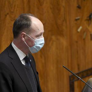 Jussi Halla-aho iklädd munskydd i riksdagens plenisal vid podiet.