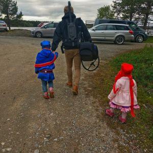 Suvi Westin puoliso Anssi Kömi kävelee saamenpukuisten lasten kanssa.