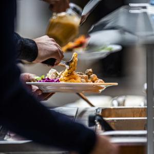 En hand lassar på mat på en tallrik vid en matbuffé.