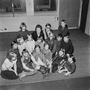 Satukaruselli -radio-ohjelman poppoota studiossa 1966. Ohjelmassa esiintyviä lapsia sekä Satukarusellikoira Mosse Murina. Porukan keskellä Toini Vuoristo.