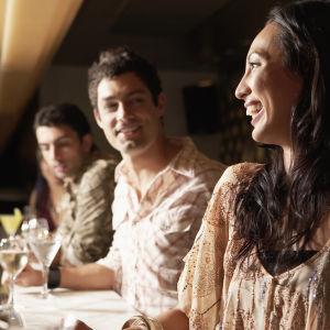 Leende kvinna i profil, två män i bakgrunden