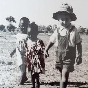 50-60-luvun kuvassa Jaakko Löytty pikkupoikana hattu päässä, lappuhaalareissa ja saappaissa, kävelee käsi kädessä kahden mekkoihin puetun namibialaistytön kanssa paahteisessa maisemassa.