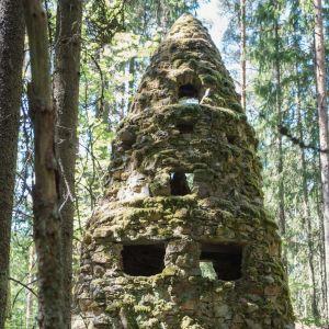 Kivistä koottu sammaloitunut suuri veistos metsässä, rakennelma, ikkuna-aukkoja
