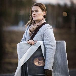 Lea (Pirjo Lonka) står med en Kristustavla under armen och ser bekymrad ut.