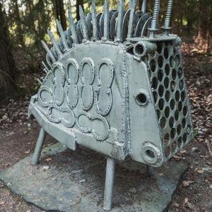 Metallskulptur står på sten i skogen.