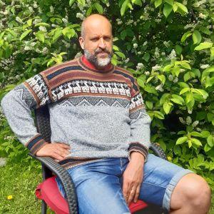 Sture Lindholm sitter i sin trädgård i Raseborg framför en hägg i blom