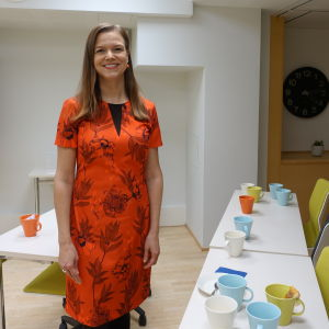 Foto på Magdalena Lönnroth som står i ett mötesrum.
