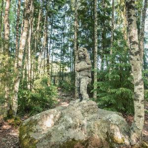 Staty på sten i skogen.