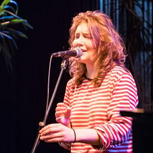 Laulaja Marey silmät kiinni, pitää kiinni mikrofonitangosta, taustalla mustaa.