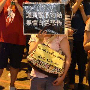 En demonstrant bär en lapp med en text om att hon inte är ett gult paket. För ett tag sedan sade poliser att de hade trott att de sparkade på ett gult paket efter att de hade misshandlat en man klädd i gula kläder.