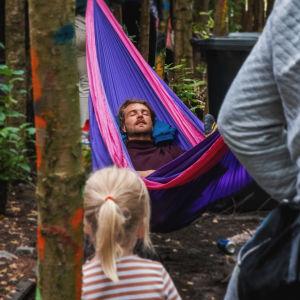 Ung man ligger och sover i hängmatta som är upphängd i två träd som växer på gammal bangård.