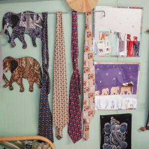 Norsukravatteja ja muita norsuaiheisia juttuja seinälle ripustettuina.