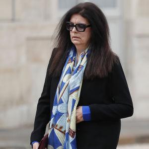 En kvinna i glasögon går. Hon tittar nedåt och ser nedstämd ut.