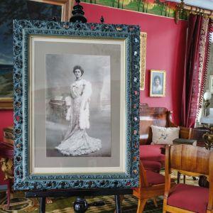 Suurikokoinen mustavalkoinen valokuva oopperalaulaja Aino Acktésta, jalustalla salissa, taustalla vanhanaikaisia huonekaluja