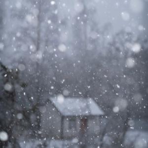 Lumisade maaseudulla mökin pihalla.
