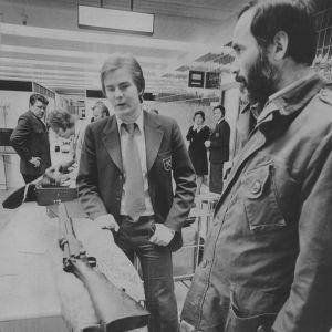 Kuusi lentokentän tullivirkamiestä ihmettelee Pentti Kronqvistin kivääriä.