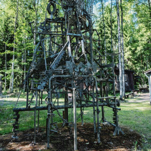 Konstverk gjord av träpinnar, metallrör, sågblad och kedjor ute på en gårdsplan med skog i bakgrunden.