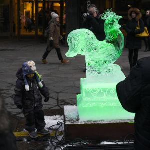 Ett barn tittar på en iskulptur av en tupp under firandet av det kinesiska nyåret 2018 i Helsingfors.