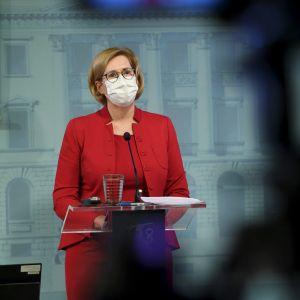 Arbetsminister Tuula Haatainen i röd kostym och ljust munskydd står bakom en talarstol i Helsingfors den 19 november.