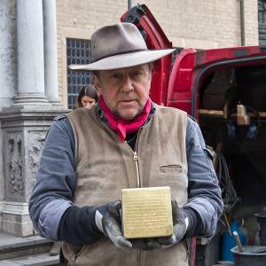 Konstnären Gunter Demnig med en så kallad stolpersteine i handen.