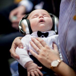 En sovande bebis i en vuxen människas famn. Bebisen har stora hörlurar som skyddar hörseln.