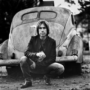 Per Gessle fotograferad framför gammal amerikansk bil.