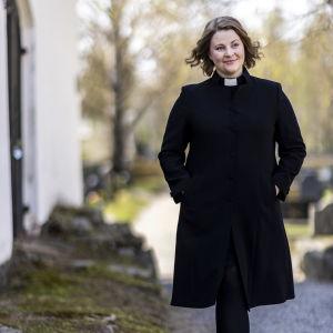 Kvinna i prästkläder som går på en grusgång.