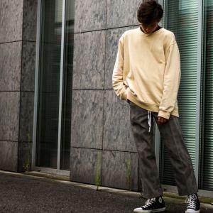 En kille med bekväma kläder poserar utomhus.