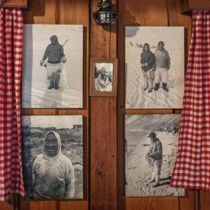 Neljä mustavalkoista valokuvaa puuseinällä. Kuvissa Grönlannin inuiitteja lumisissa maisemissa.