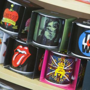 Kaffekoppar på med bandlogon butikshylla. Rolling Stones, Alice Cooper, Sex Pistols, ZZ Top, The Who-koppar.