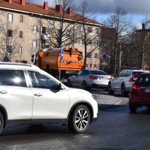 Imulakaisinkone ajaa autoletkan edessä liikenneympyrässä.