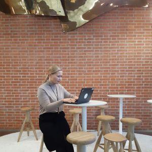 Foto på Henrika Vikman som sitter uppflugen på en hög pall och jobbar på sin bärbara dator.