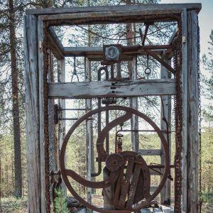 Puusta ja ruostuneesta raudasta koottu neliömäinen rakennelma