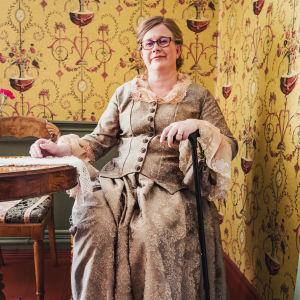 Piia Vähäsalo sitter på handelshusets cafésida iklädd en klänning i äkta 1800-tals anda samtidigt som hon lutar sig mot sin gångkäpp.
