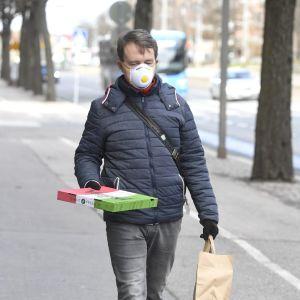 En man som har ett andningsskydd och håller i en pizzakartong ute på gatan.