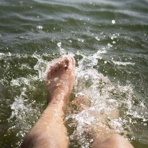 Varpaat polskuttelee vedessä.