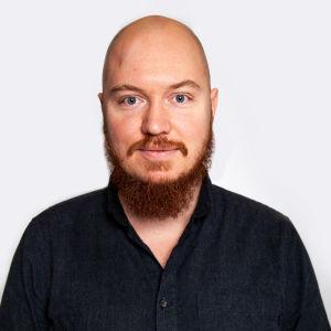 En närbild av en skallig man med rött skägg.