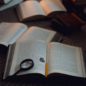 Uppslagen bok med ett förstoringsglas och en blyertspenna.