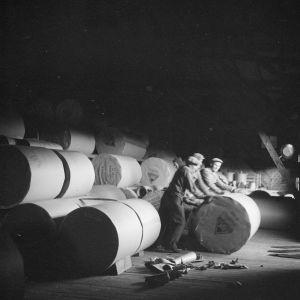 Arbetare hanterar pappersrullor på en pappersfabrik 1947. Svartvitt foto ur Museiverkets samlingar.