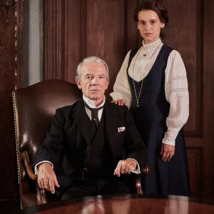 Lothar von Faber (Martin Wuttke) istuu nojatuolissa, Ottilie von Faber-Castell (Kristin Suckow) seisoo hänen takanaan. Kuva sarjasta Lyijykynätehtaan tyttö