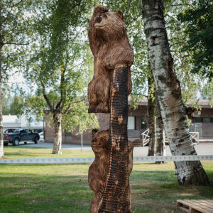 Puuveistoksessa kaksi karhua kiipeämässä allekkain puunrungolla