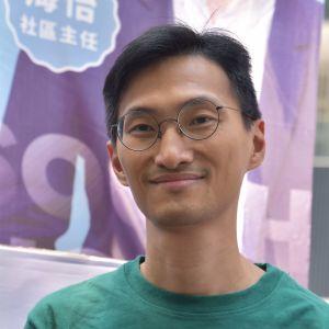 Eddie Chu ler. Han har runda glasögon, svart hår, och en grön tröja med vita tecken på.
