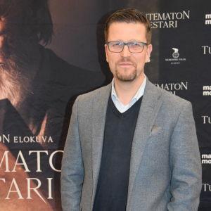 Klaus Härö poserar framför planschen till Okänd mästare.