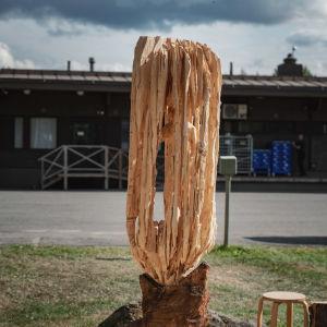 Puinen veistos, jossa teksti Kontion vihellys, alaosassa karhu, jonka suusta lähtee puista kehikkoa muistuttava muoto, sisällä ihmishahmo