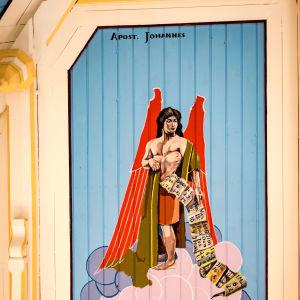 Apostoli Johannesta esittävä kirkasvärinen maalaus kirkon sisäkatossa, vatsasta tulee paperirulla, säkeitä.