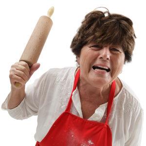 en äldre kvinna med förkläde och bakkavel i handen tittar ilsket in i kameran.