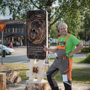 Mies poseeraa puuveistoksen edessä, joka muistuttaa älypuhelinta, jonka ruudulla karhu suu auki