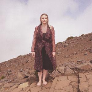YleX Nosteessa -artistin Sirénin promokuva, jossa laulaja seisoo silmät kiinni hiekkaisessa mäessä portaalla.